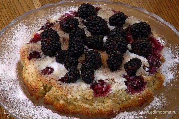 Готовый пирог остудить, затем перевернуть на блюдо, посыпать сахарной пудрой и украсить оставшейся ежевикой.