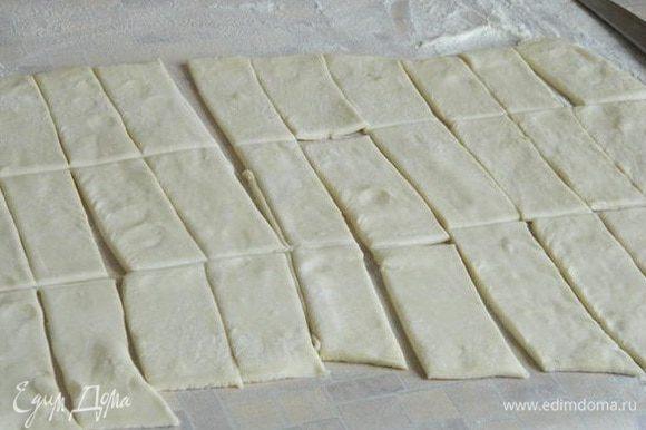 Тесто разморозить и раскатать в одном направлении. Нарезать на полоски, шириной примерно 1,5-2 см, потом на прямоугольники.