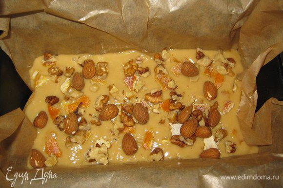 Форму высылаем пекарской бумагой. Выливаем туда тесто. Нарезаем цукаты. Добавляем орехи.