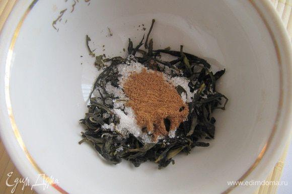 Сухой чай смешать с корицей и сахаром. Положить в заварочный чайник, залить кипящей водой на 1/2 объема,дать настояться в течение 10 минут, Затем влить кипяток,накрыть чайник салфеткой и оставить на 5 минут