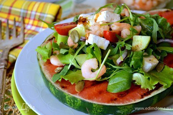 Для сервировки салата выложите на блюдо арбузную скибку, сверху выложите листья салата, чередуя их с креветками, кусочками феты и огурцом. Украсьте слегка тыквенными семечками, немного посолите, сбрызните оливковым маслом и уксусом бальзамико (тем, что очень густой по консистенции, почти как соус...)