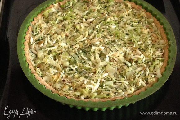 Убрать бумагу вместе с фасолью и выложить на основу капустную начинку, разровнять.