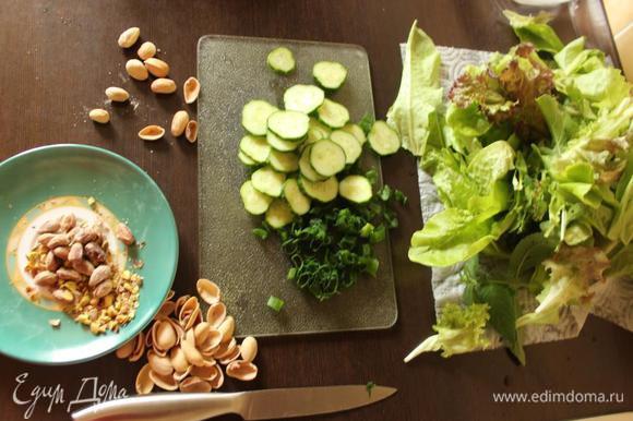 Получается 2 большие или 3 средних порции. Салатный микс (у меня листовой салат и рукола) и овощи моем и обсушиваем. Пару небольших огурчиков режем тонкими кружочками, 2 пера (в ингредиентах - стебель) зеленого лука измельчаем, орешки (у меня соленые) очищаем и крупно рубим.