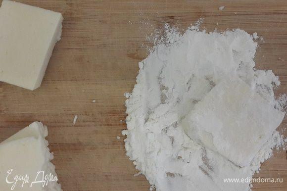 Сыр нарезать крупно. Обмакнуть сначала в муку, затем в соль. В сковороду наливаем 1 столовую ложку растительного масла и кусочек сливочного, выложить сыр и обжарить до золотистого цвета (буквально 15 секунд с каждой стороны). Выкладываем на бумажное полотенце. Из апельсина выжимаем сок, добавляем его в сковороду, где жарился сыр. Готовим, пока не загустеет. Духовку разогреть до 180 градусов. Выложить на противень сыр, полить соусом. Посыпать сверху сахаром и кунжутом. Выпекать 15–20 минут