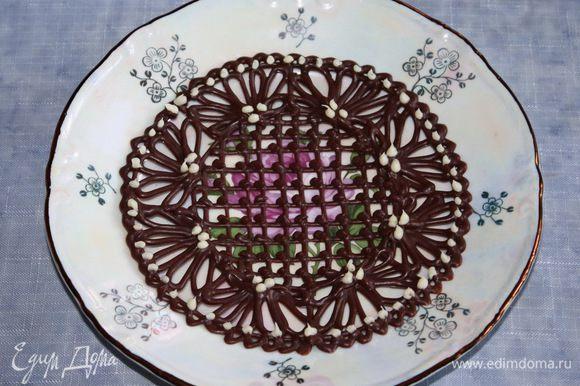 Даем блюдцу немного застыть, затем наносим капельки белого шоколада, который тоже надо растопить. Даем полностью застыть шоколаду при комнатной температуре. Затем осторожно перекладываем блюдце на сервировочную тарелку.