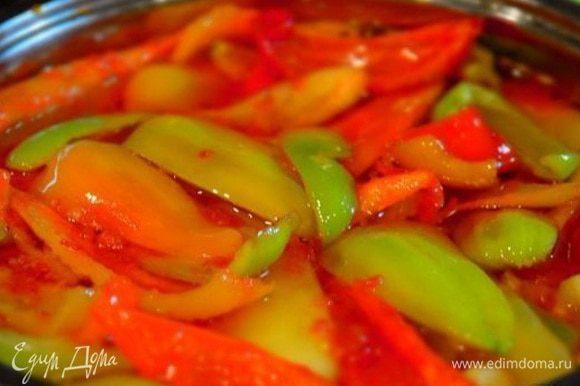 Добавить в кастрюлю подготовленный перец, перемешать аккуратно и проварить 10 минут. Разложить перец по стерилизованным банкам, залить томатным соком и закатать под железные крышки.
