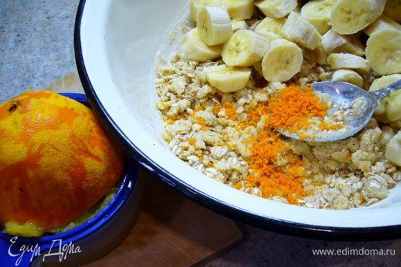 Бананы очистить (взять не очень крупные), порезать на толстые кружочки, добавить к тесту. Апельсин вымыть, натереть цедру, выжать сок. Добавить в миску, перемешать.