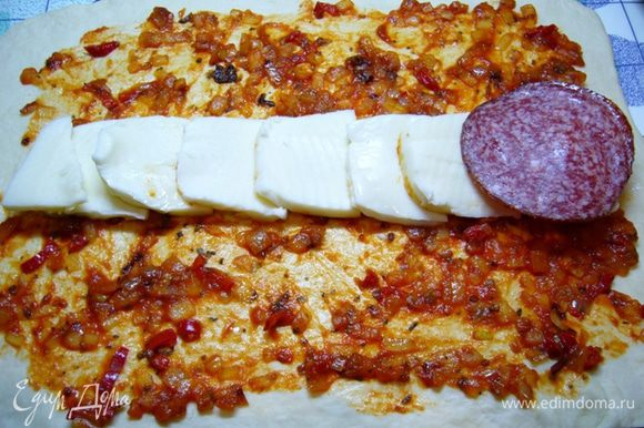 Духовку разогреть до 200 град. Распределить по нему соус, немного отступая от краев теста. В центре сделать «дорожку» из сыра, сверху – из колбасы.