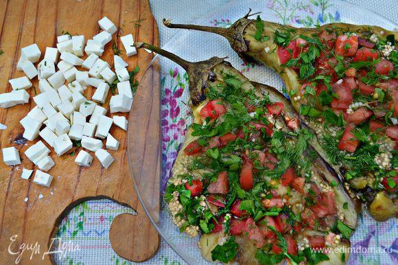 На баклажаны выложить чеснок, помидоры, рубленную зелень и нарезанную кубиками фету. Вместо феты можно использовать брынзу или адыгейский сыр, также вы можете не нарезать кубиками, а покрошить поверх помидоров.
