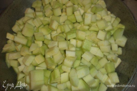 Кабачки очистить, нарезать кубиками, выложить их в смазанную растительным маслом форму для запекания.