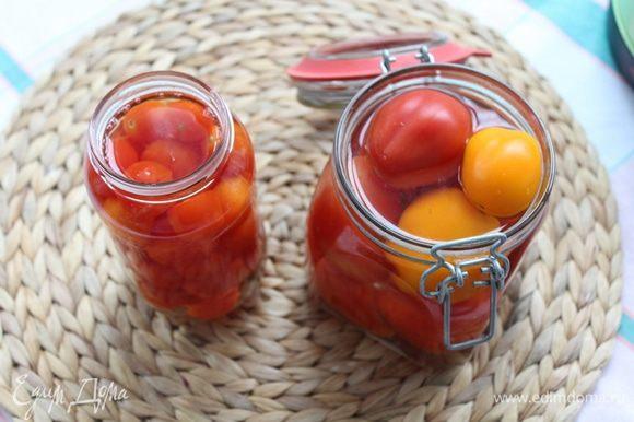 В стерилизованные банки уложите помидоры черри и залейте кипятком на 5 минут.