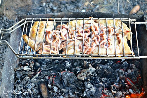 Выложить на смазанную маслом решётку гриля нафаршированные тушки кальмаров и щупальцы, ставим на горячие угли. Готовить 10 минут, переворачивая периодически решётку.