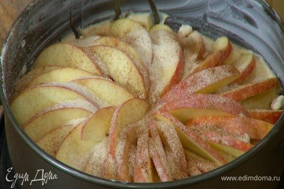 На тесто по кругу веером выложить яблочные дольки, посыпать их оставшимся сахаром и корицей.