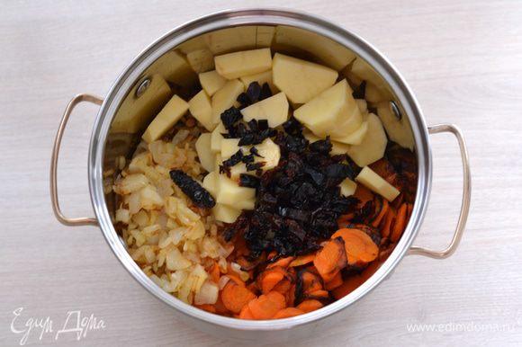 В глубокую кастрюлю насыпать чечевицу, выложить лук с чесноком, морковь и картофель. Залить водой, посолить, поперчить, добавить лавровый лист. Варить примерно 35 минут на среднем огне.