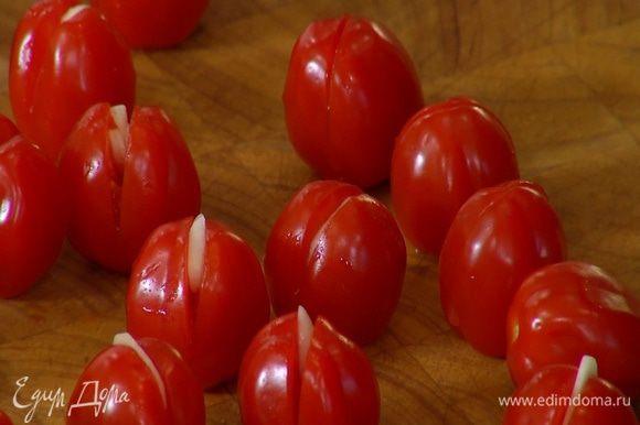 Чеснок почистить, нарезать тонкими ломтиками и вставить в разрезы помидоров.