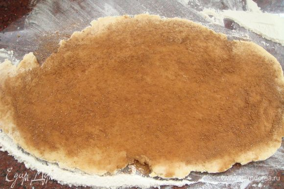 Раскатать часть теста в пласт. 2 ст ложки корицы смешать с 1 ст ложкой сахара, выложить на пласт теста и ладонью распределить равномерно по поверхности.