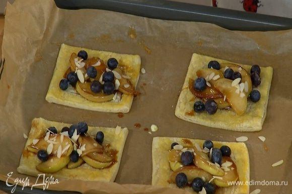 Подпеченное тесто вынуть из духовки, в центр каждого квадратика выложить карамелизированные яблоки, присыпать их голубикой и миндалем.