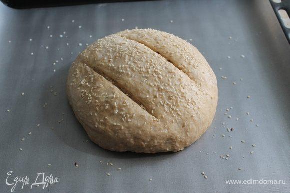 Сделать пару разрезов перед выпечкой, смазать хлеб молоком и посыпать кунжутом.