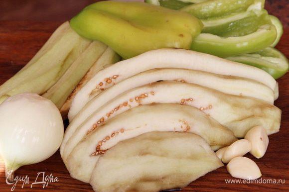 Баклажаны очищаем, нарезаем пластинами толщиной 0.5 см. Перец, лук и чеснок чистим.