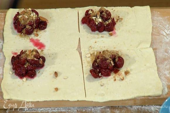 На один угол теста, отступая от края по 1 см, выложить вишню и посыпать орехами с сахаром и корицей.