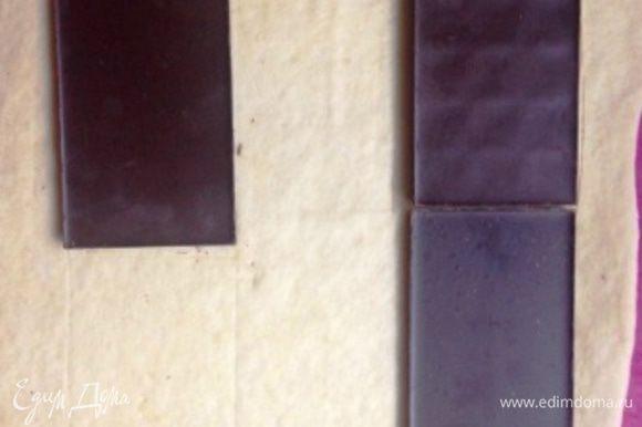 Обмять и разделить пополам. Половину теста раскатать на пропыленном мукой пергаменте в прямоугольник, по ширине равный 3 плиткам шоколада и 2 по длине. Лишнее тесто обрезать (это будущие булочки).