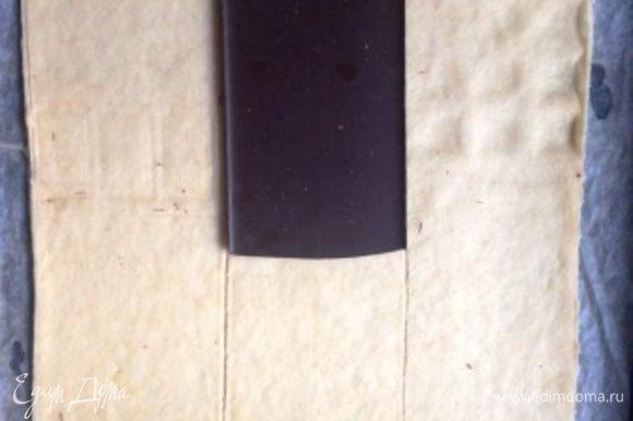 Перенести прямо на пергаменте на противень. Уложить 1,5 плитки шоколада ровно в центре полученного прямоугольника. Обвести контур.