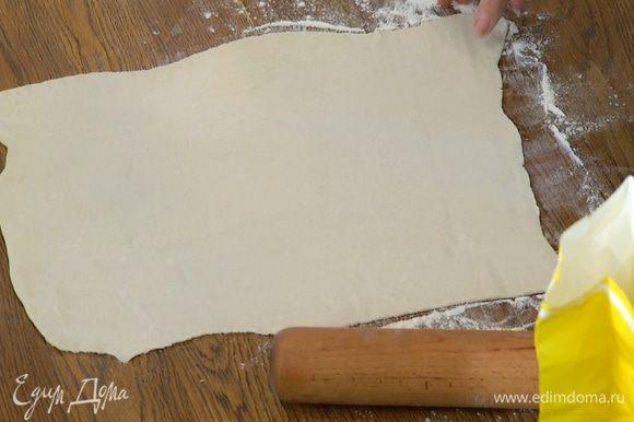 Рабочую поверхность присыпать оставшейся мукой и тонко раскатать тесто.