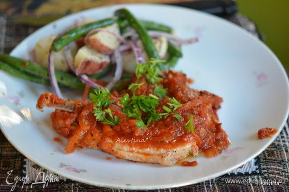 Подаем свинину к столу с готовым гарниром, полив томатным соусом. Посыпать сверху зеленью. Приятного аппетита!