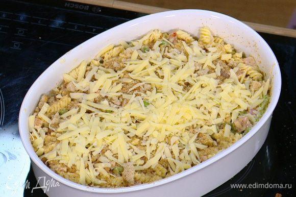 Выложить макароны в форму, утрамбовать и присыпать сверху натертым сыром и оставшимися сухарями.