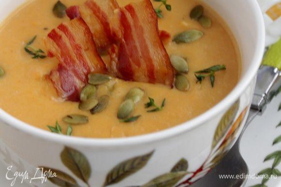 Суп подать с кусочками бекона, тыквенными семечками, украсьте листочками тимьяна.