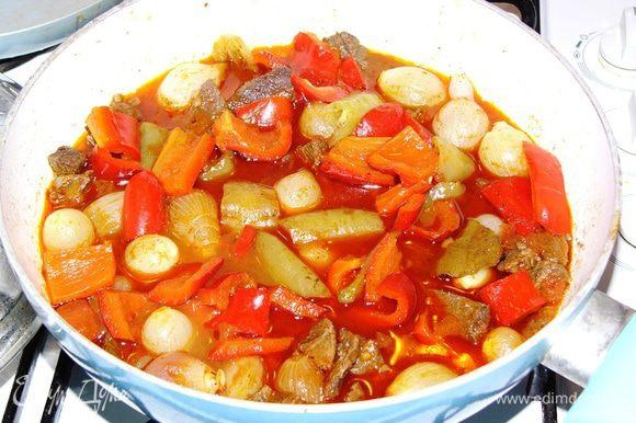 Когда мясо по мягкости приближается к готовому, добавляем в сотейник ощищенный лук-шалот, нарезанный перец, очиценные зубчики чеснока, 1 нарезанный помидор. Если есть томаты в собственном соку, добавляем вместо свежего помидора их. Хорошо приправить блюдо специями для мяса и тушения. Посолить.