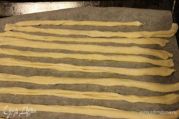 Нарезать тесто на тонкие полоски и каждую полоску скрутить в тонкий жгут движениями пальцев как будто скручиваем нитку. Так проделываем до конца. Выкладываем палочки на лист, смазанный маслом и ставим на среднюю полку духовки, разогретой до 180 С. Запекаем около 10-15 минут. В процессе выпечки пару раз сбрызгиваем палочки водой из пульверизатора.