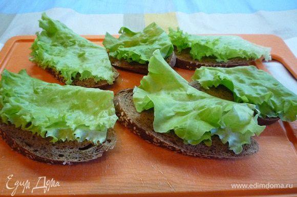 Яйца отварить и почистить. Хлеб нарезать тонкими ломтиками, каждый ломтик смазать сливочным маслом, положить сверху листики салата и одному ломтику лосося на каждый бутерброд.