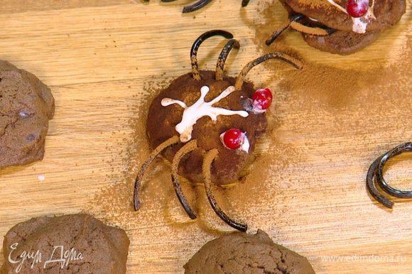 Присыпать паучков какао, глазурью нарисовать глазки, а на спинках различные узоры, сверху выложить ягоды смородины.