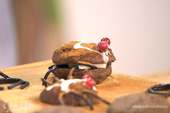 Оставшееся печенье остудить, у половины печенья смазать плоскую сторону кремом, разложить лакричные палочки, так чтобы их края свешивались, как лапки, и накрыть несмазанным печеньем. Посыпать сверху какао и сделать глазурью рисунок на спинках паучков.