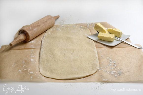Тесто переложить на лист бумаги для запекания и раскатать в прямоугольник. Оставшееся сливочное масло разделить на 3 части (масло должно быть мягким).