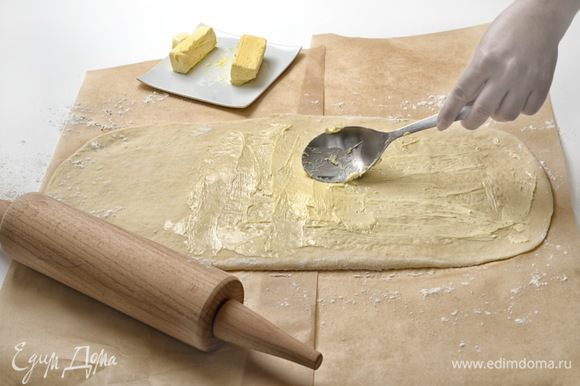 Намазать 1/3 масла на 2/3 поверхности теста, отступив от краев по 2 см. Несмазанную поверхность завернуть на половину смазанной поверхности и прикрыть оставшейся смазанной поверхностью.