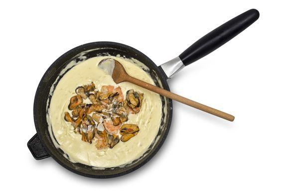 В полученный соус положить очищенные креветки и мидии и тушить еще 1 минуту.