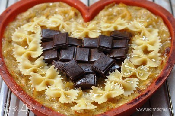 Но можно и украсить нашу запеканку шоколадом. На горячую запеканку уложила отложенные, отварные макароны-бантики и кусочки шоколада. Поставила в горячую духовку на 5-7 минут, следя пока растопится шоколад.