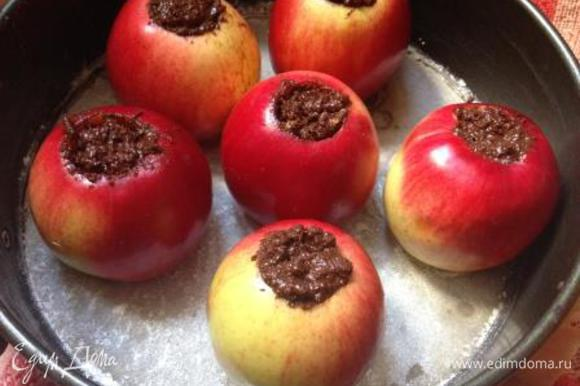 Начинить яблоки шоколадной массой, поставить в застеленную пергаментом и смазанную маслом форму.