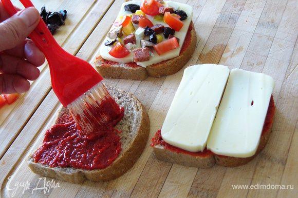 С помощью кисточки намажем хлеб перцовой пастой. Сверху положим пластины сыра. На сыр разложим начинку. Положим сверху несколько кусочков моцареллы или брынзы.