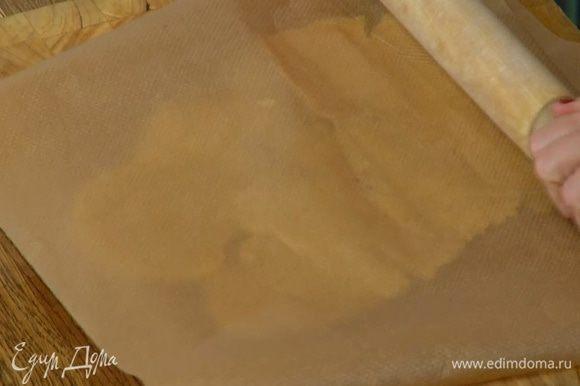Охлажденное тесто раскатать в пласт (можно поместить его между двумя листами бумаги для выпечки).