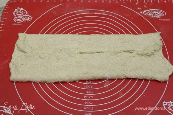 Затем присыпаем рабочую поверхность немного мукой. Выкладываем тесто. Раскатываем в квадрат, примерно 40х40 см. Складываем тесто к середине.