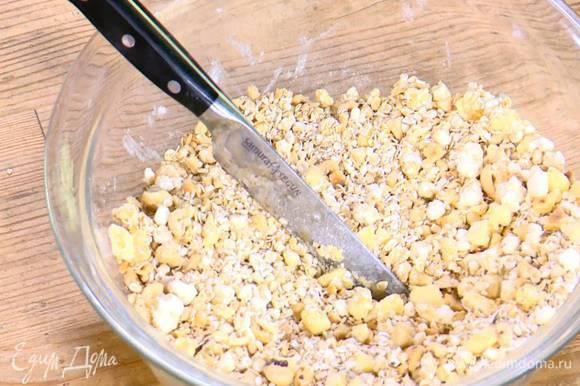 Приготовить тесто: сливочное масло соединить с творогом, мукой, сахаром и солью, все порубить ножом в крошку, затем добавить овсяные хлопья, фундук и порубить еще немного.