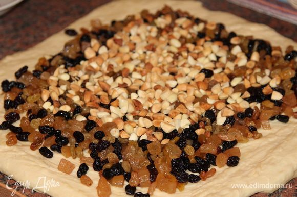 Теперь раскатываем тесто в квадрат и высыпаем на него подготовленные изюм с цукатами и орехи.