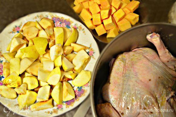 Яблоки помойте, нарежьте дольками. Тыкву помойте, очистите и порежьте кубиками. Переложите яблоки с тыквой в миску, слегка подсолите, добавьте свежемолотый перец и перемешайте. Начините утку, скрепите отверстие зубочистками.