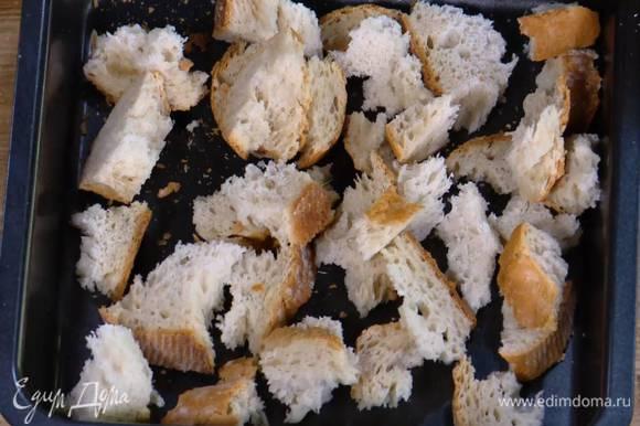 Приготовить крутоны: хлеб поломать руками на неровные кусочки и выложить в небольшой глубокий противень.