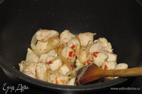 Разогреем в воке или сотейнике, растительное масло, обжарим в нем острый перец и чеснок в течении 30 секунд, добавим кусочки курицы и репчатый лук. Жарим 5 минут, постоянно помешивая.