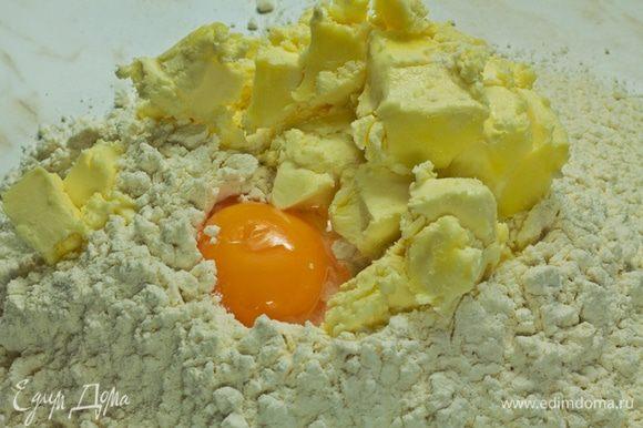 Муку просеять горкой, в углубление всыпать пудру, добавить яичный желток, нарубленное мелкими кубиками масло. Размять руками, начать замешивать, примешивая муку от краев к центру.