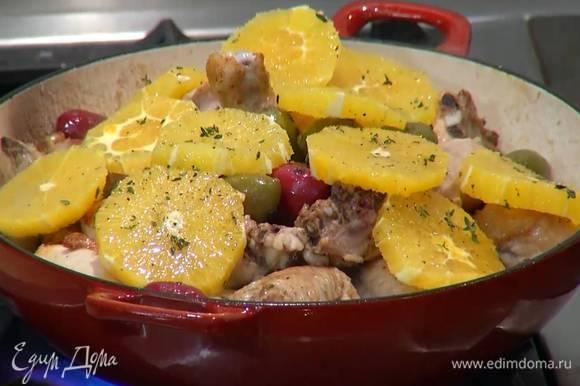 Добавить к курице оливки, сверху выложить апельсиновые кружки и тушить все до готовности под приоткрытой крышкой, чтобы выходил пар.